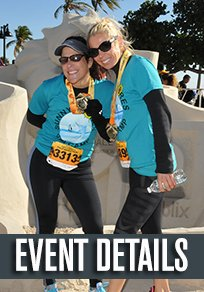 two runners in teal shirts with medals in front of a custom sandcastle carving